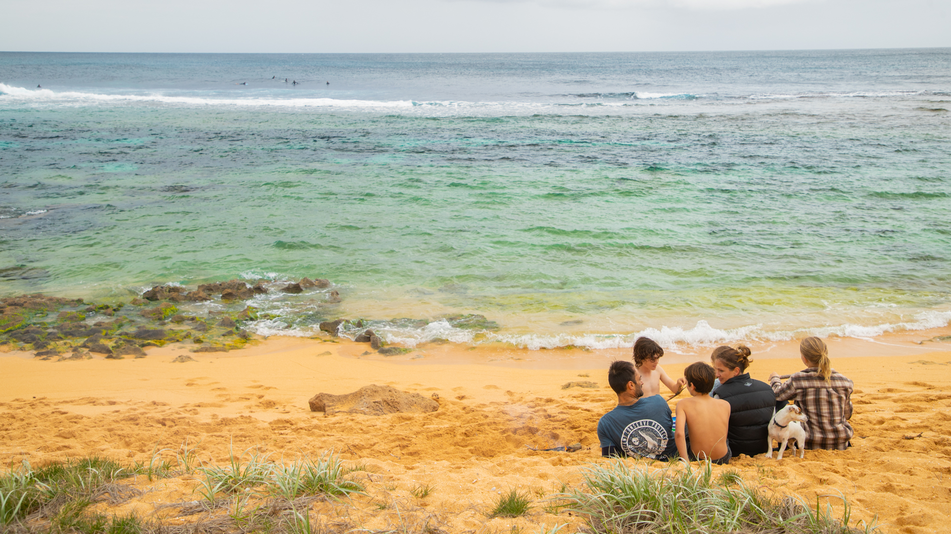 Family with their dog sitting on the shore with gentle waves breaking over rocks and the golden sand. Surfers in the water are visible in the distance.