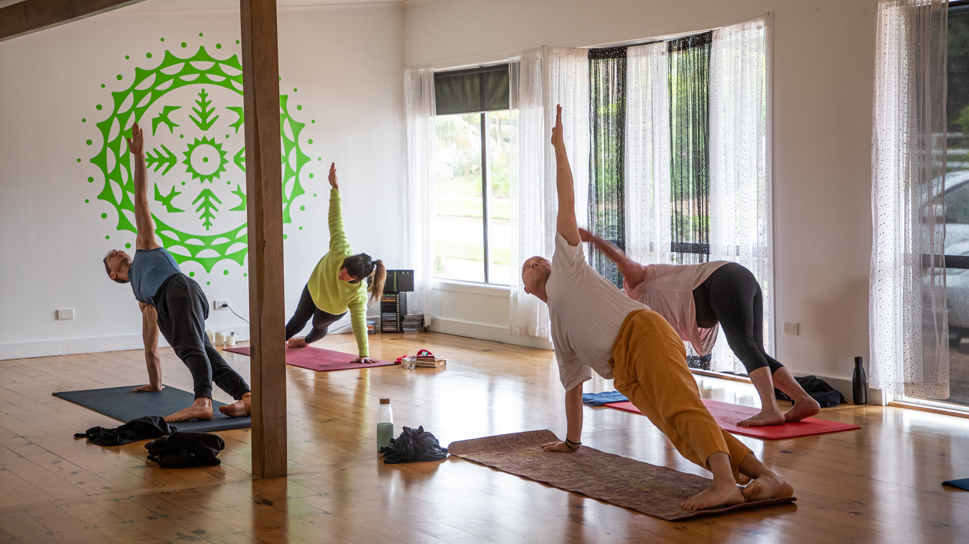 Group of young travelers relaxing and enjoying a yoga class in a studio. They are holding a side plank.