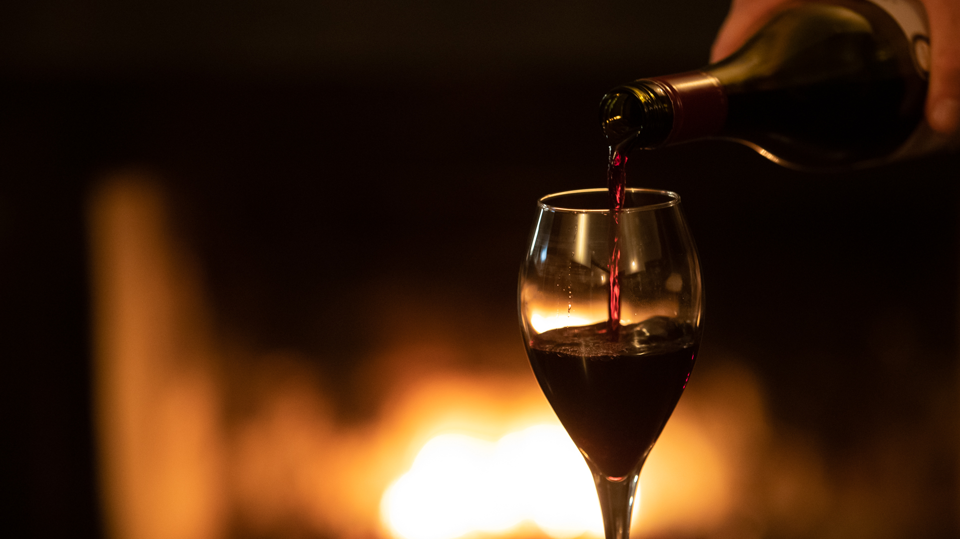 A glass of red wine is being poured in front of an out-of-focus burning fireplace in the background.