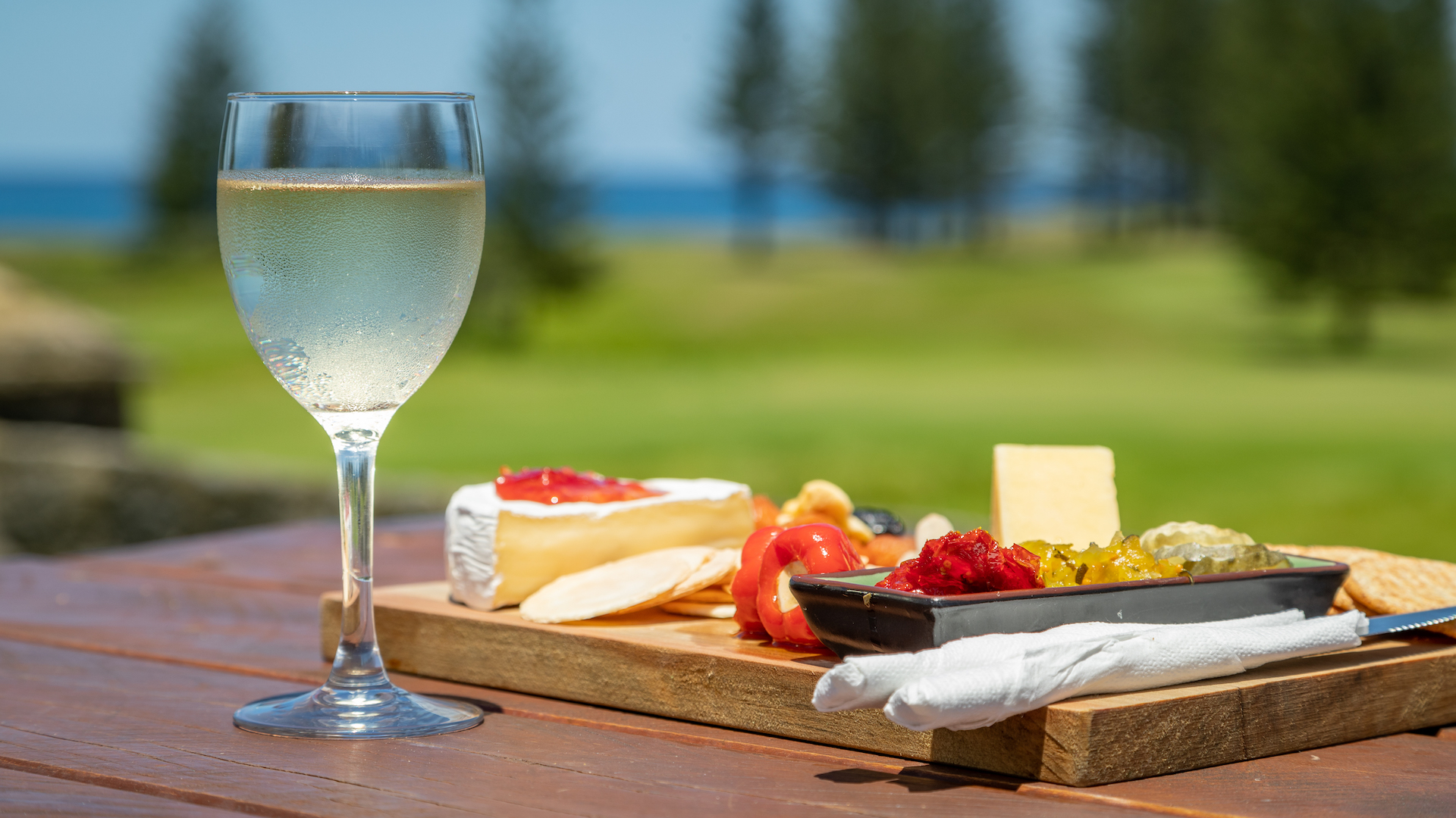 An antipasto platter and a glass of white wine rest on a wooden table on a sunny day with the ocean in the distance.