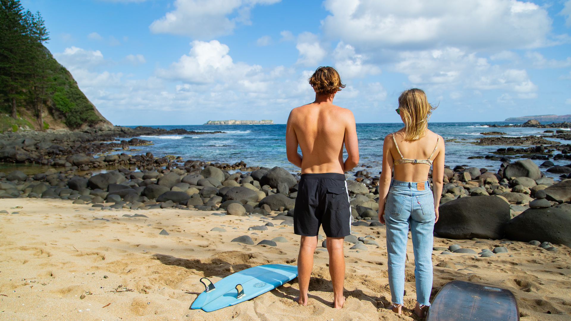 Boy in board shorts and girl in bikini top and jeans stand on beach, staring out at ocean with surfboards at their sides.
