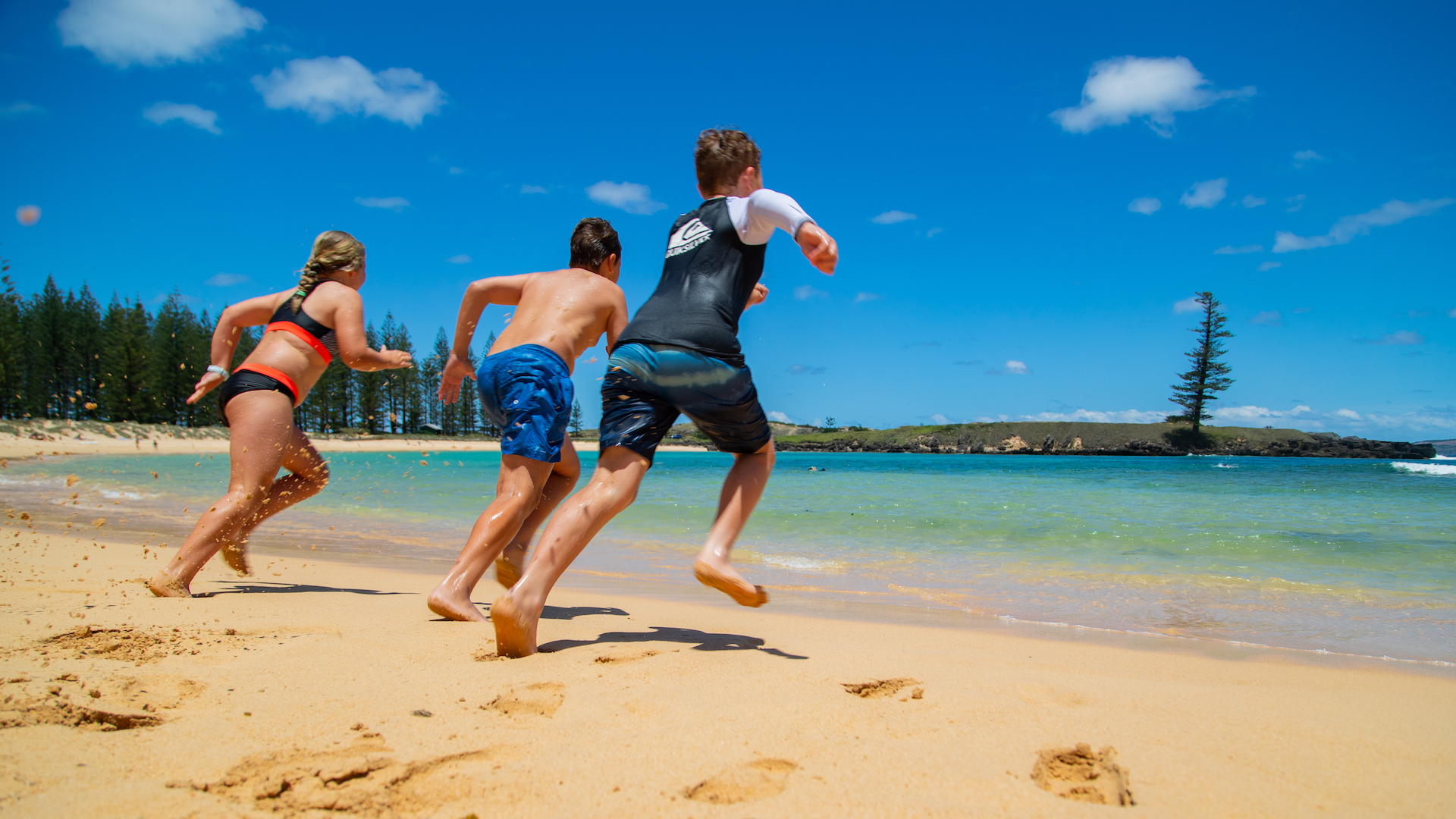 Three children sprint towards calm, clear ocean in a sandy bay. Norfolk pine forest in background, deep blue sky overhead.
