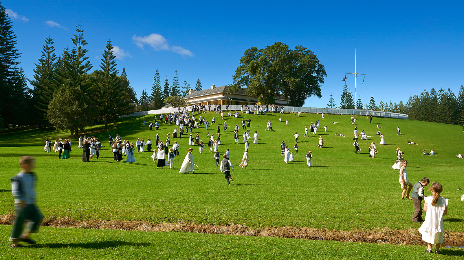 Large group of Bounty Day attendees walking down a sloping green hill in traditional white costumes.