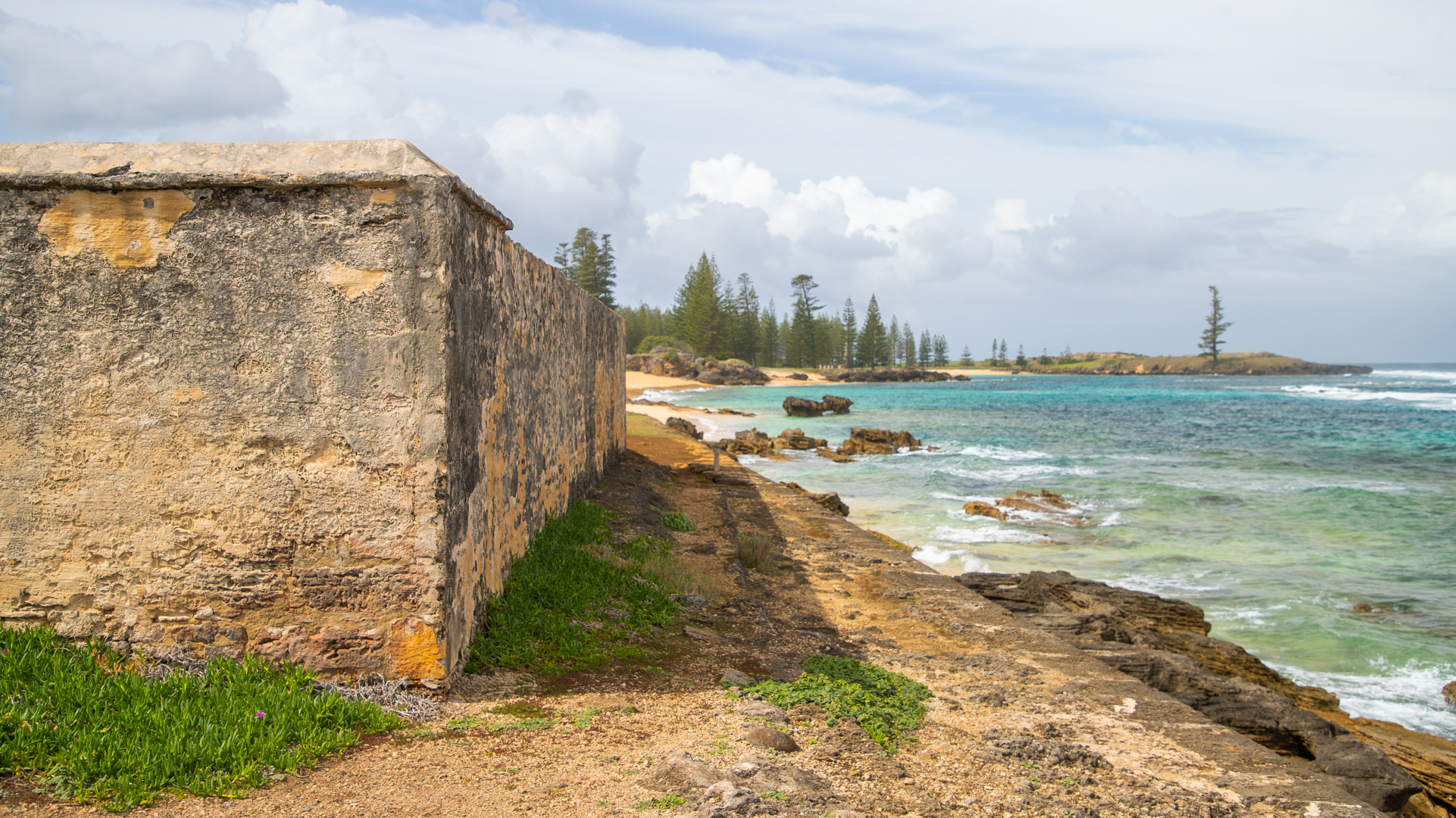 Historic ruins backing onto blue shallow waters with Norfolk Pine trees in the background.