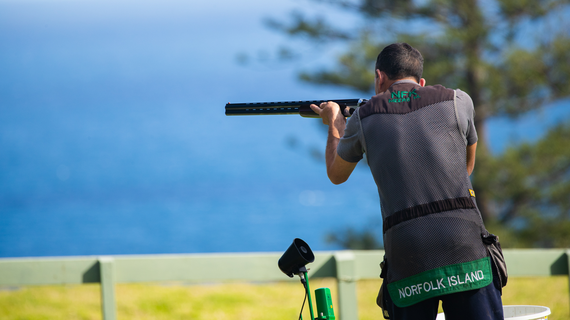 Back view of a man pointing a long double-barelled gun. He is wearing a dark coloured vest with green trim. The words Norfolk Island are printed in white.