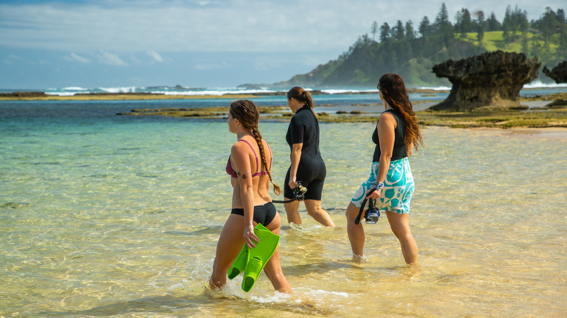 Three women are walking into the shallow turquoise sea holding masks, snorkels and flippers. There are waves in the distance and a rock formation to the right.