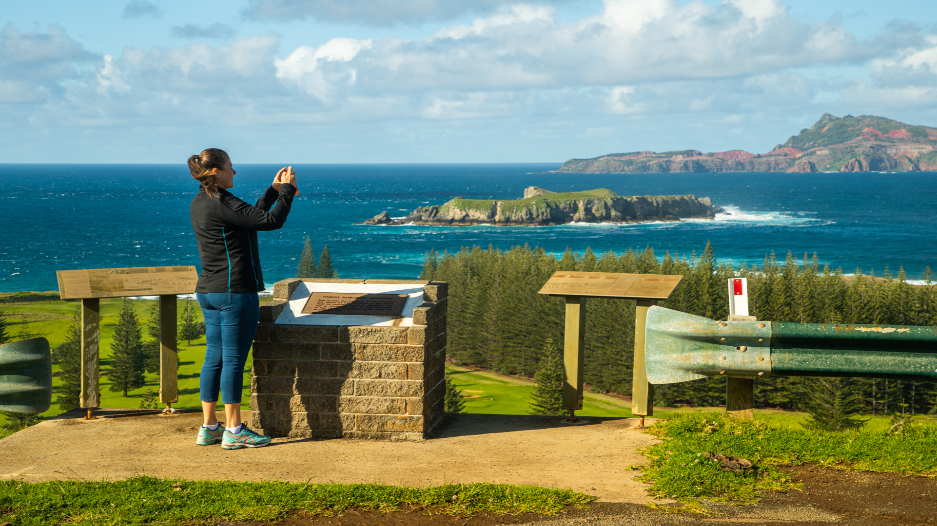 Woman in activewear taking photo from lookout point. Norfolk pine forest meeting ocean with bare rocky island in background.