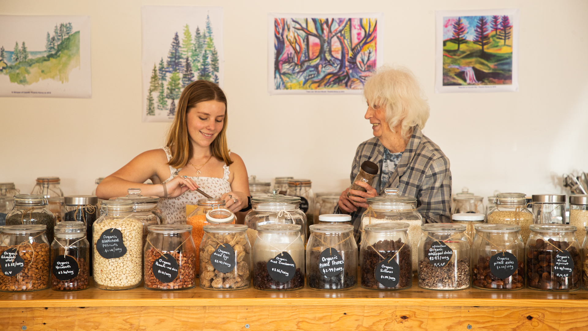 A young woman and an elderly woman smiling as they organize organic food and pantry items into mason jars.