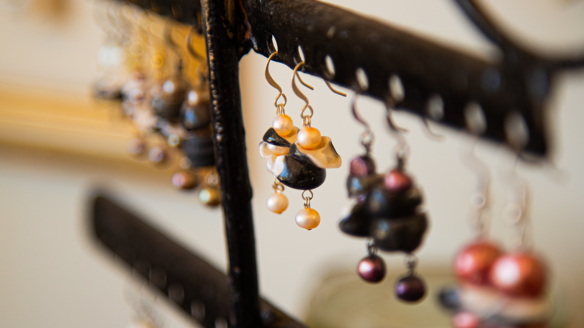 A selection of handcrafted earrings hooked on a black jewellery stand.