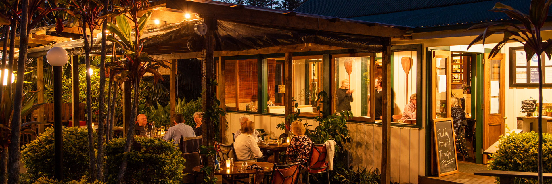 A relaxed evening alfresco dining scene set among a tropical garden. There are several diners both in and outside the re