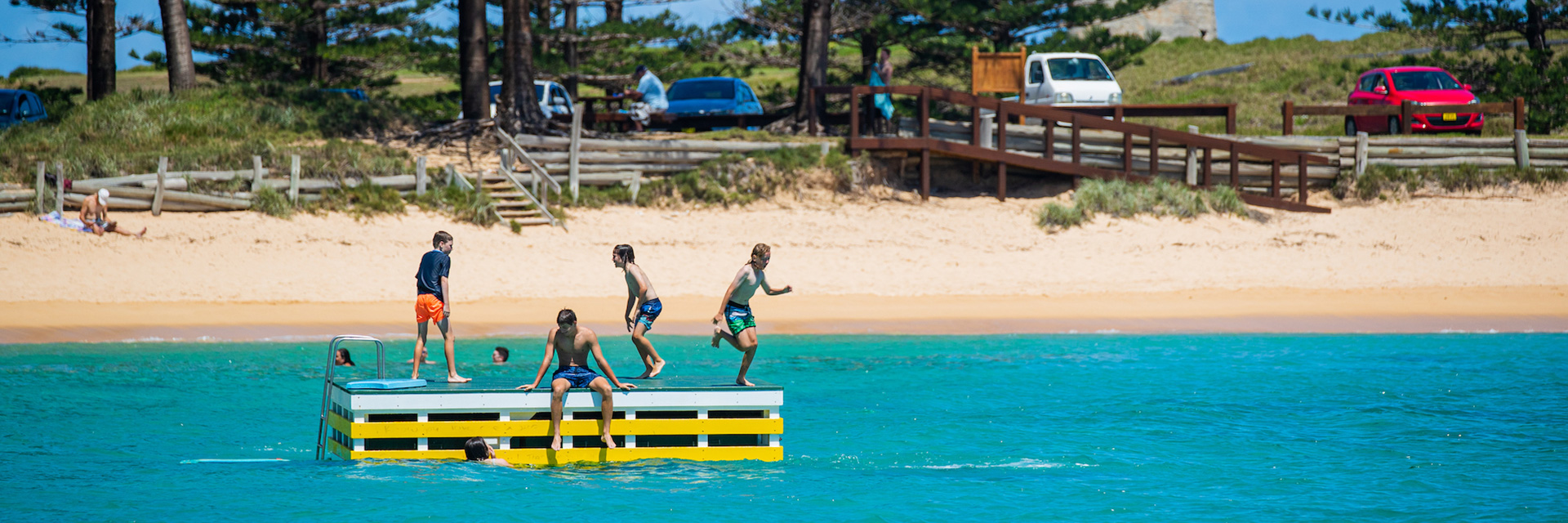 Four boys play on colourful pontoon in calm, clear ocean. Golden beach leads to pine trees and cars parked in background