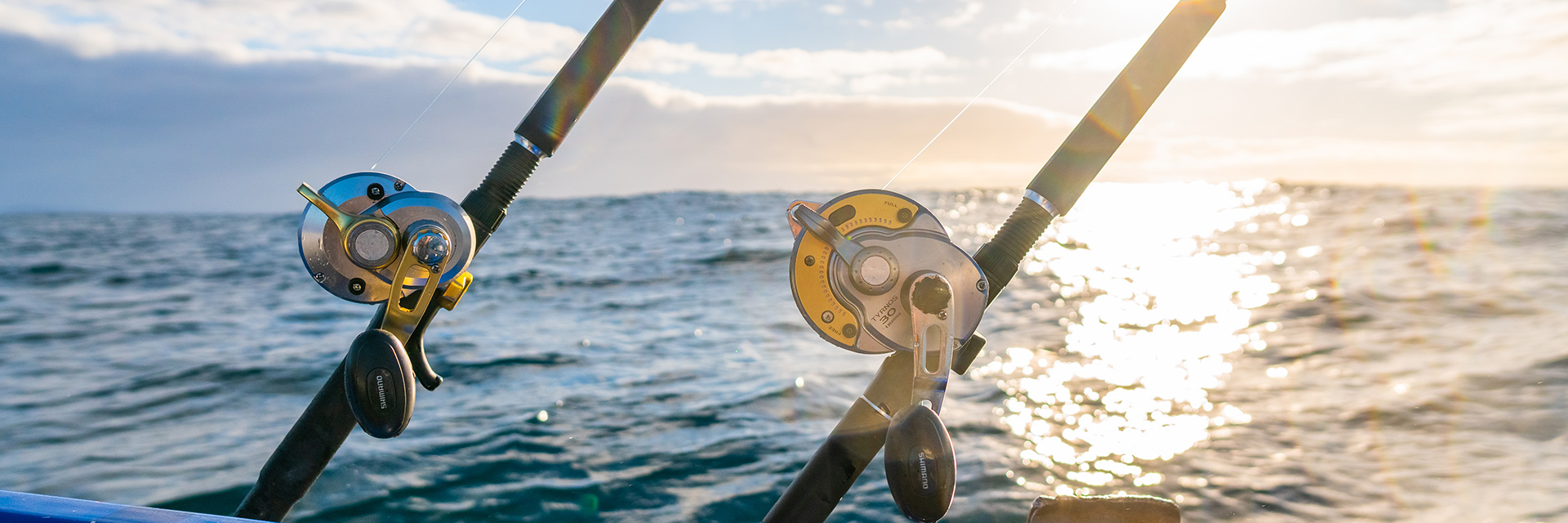 Close-up of two fishing rod reels, poles and handles. Sunlight reflects on the sea behind.