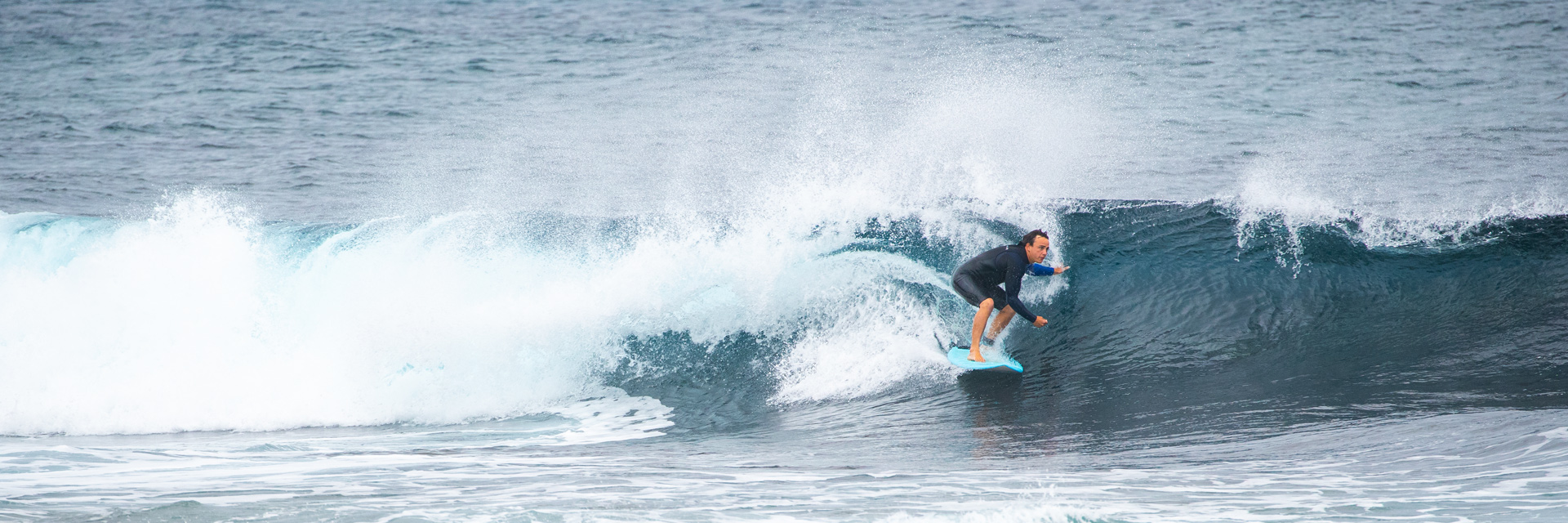 Man in black wetsuit riding an ocean wave. He is crouched on a light blue surfboard.