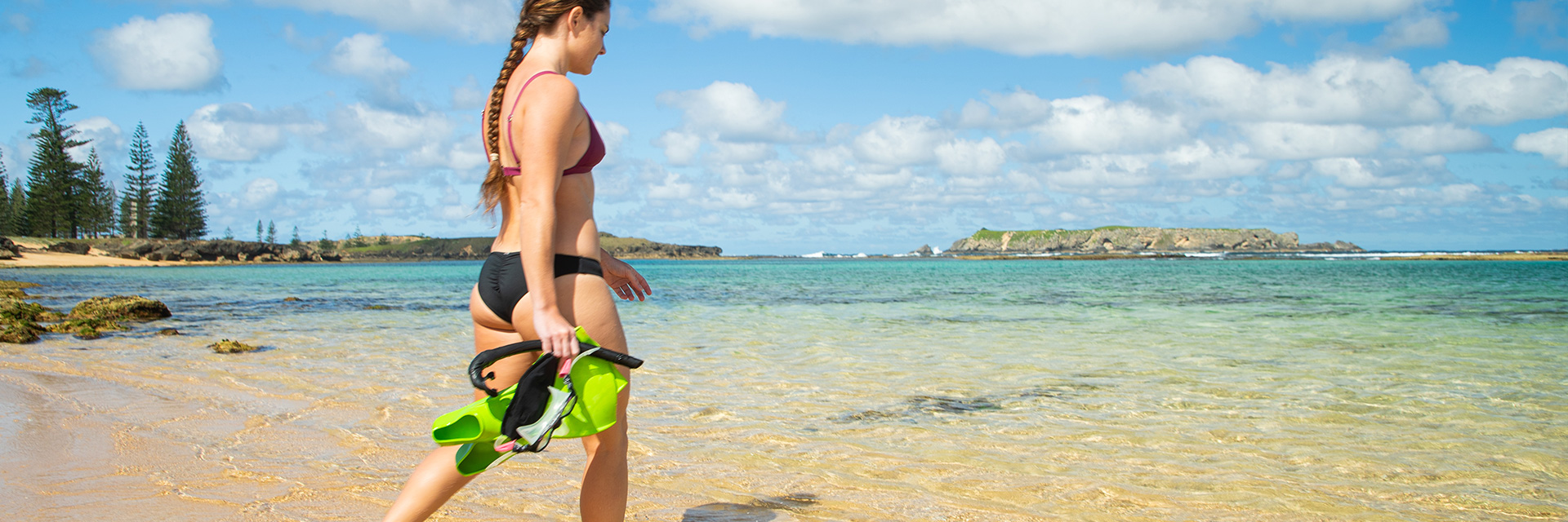 A woman in a bikini walking on the sand into the shallow sea. She is holding a snorkel, mask and flippers. An island in