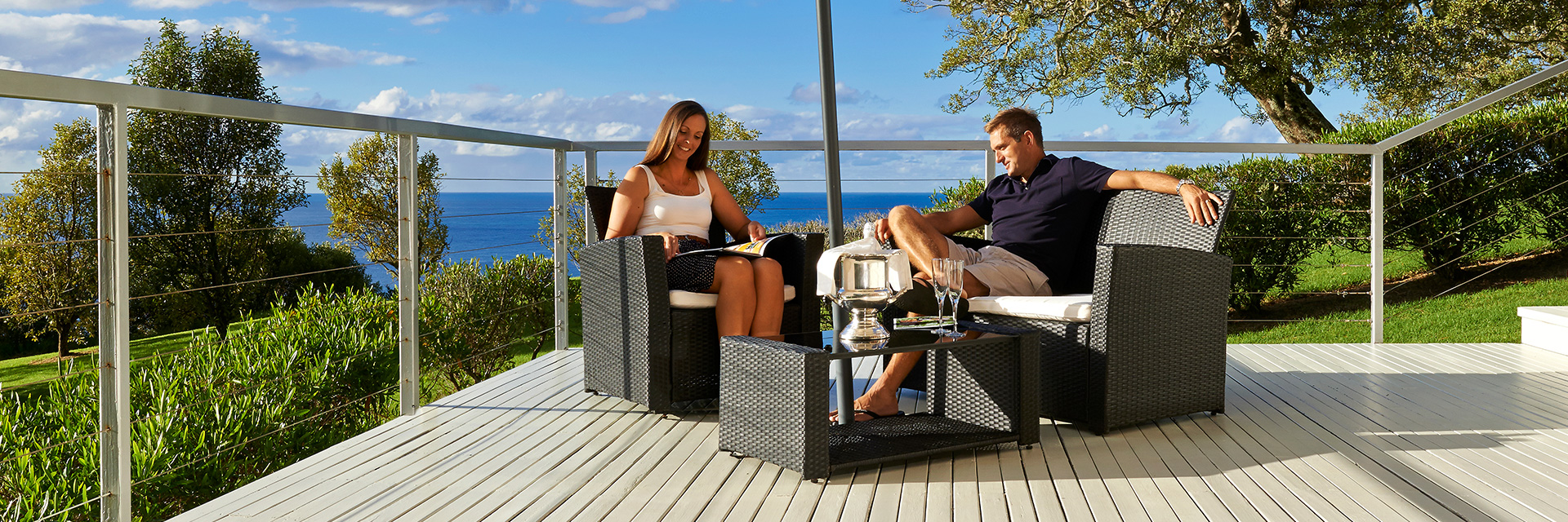 Smiling woman in white dress and man in black polo shirt sit on black wicker chairs on verandah. Trees and ocean behind