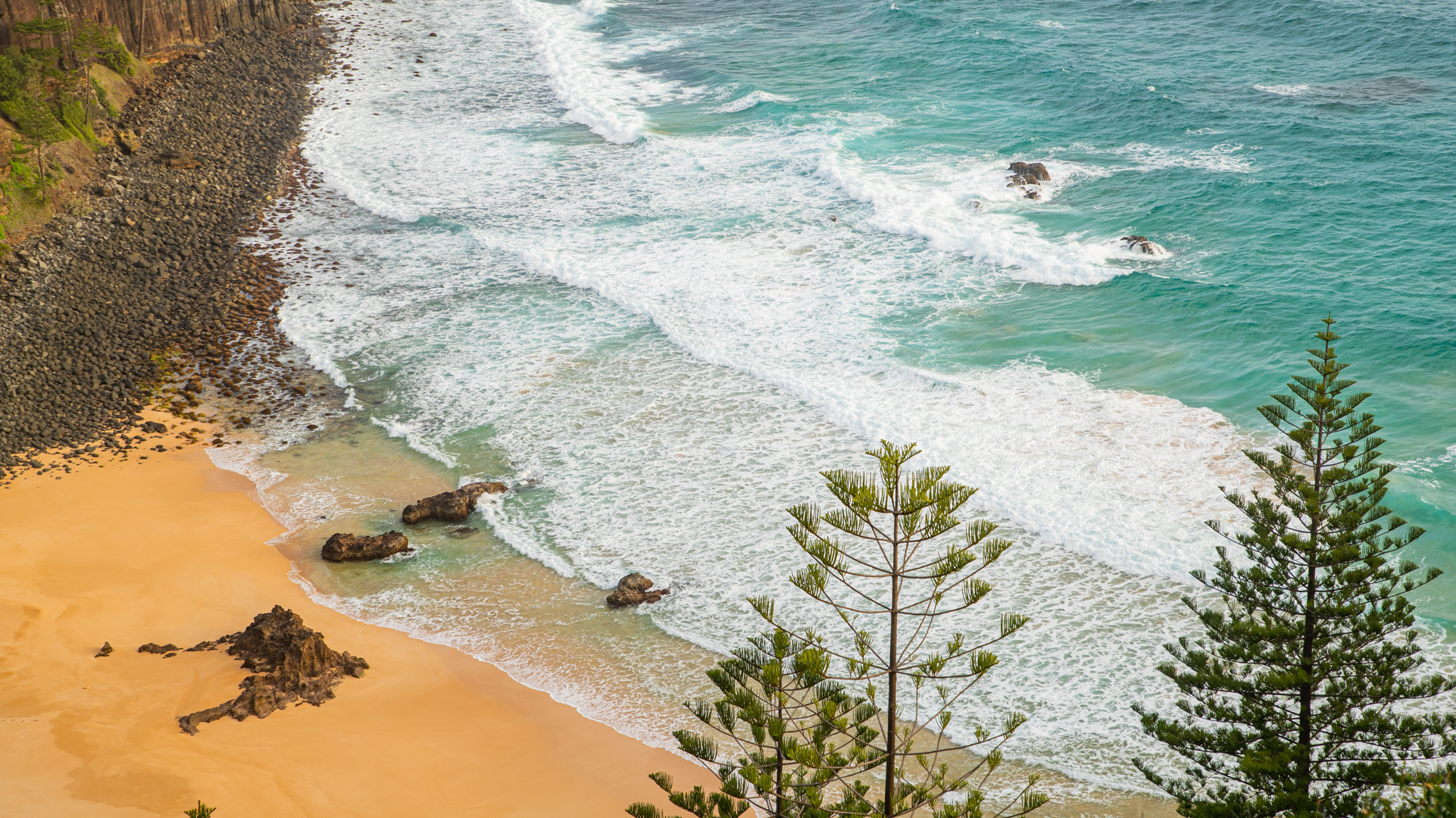 Aeriel view of Anson Bay with waves breaking on golden sand and two pine trees in the foreground.
