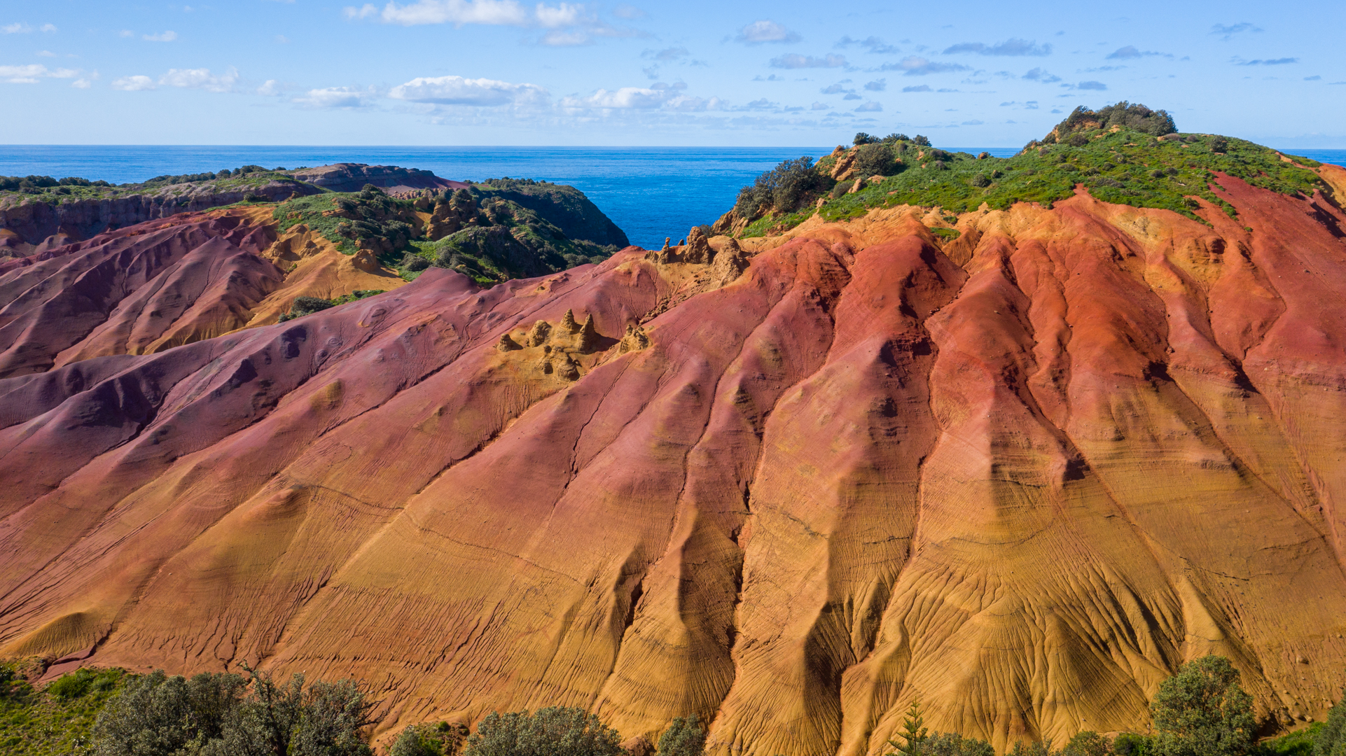 Huge rock formations in a dome shape with many vertical indentations caused by erosion. The orange, rust, ochre and pink hues of the rock are layered like a rainbow.