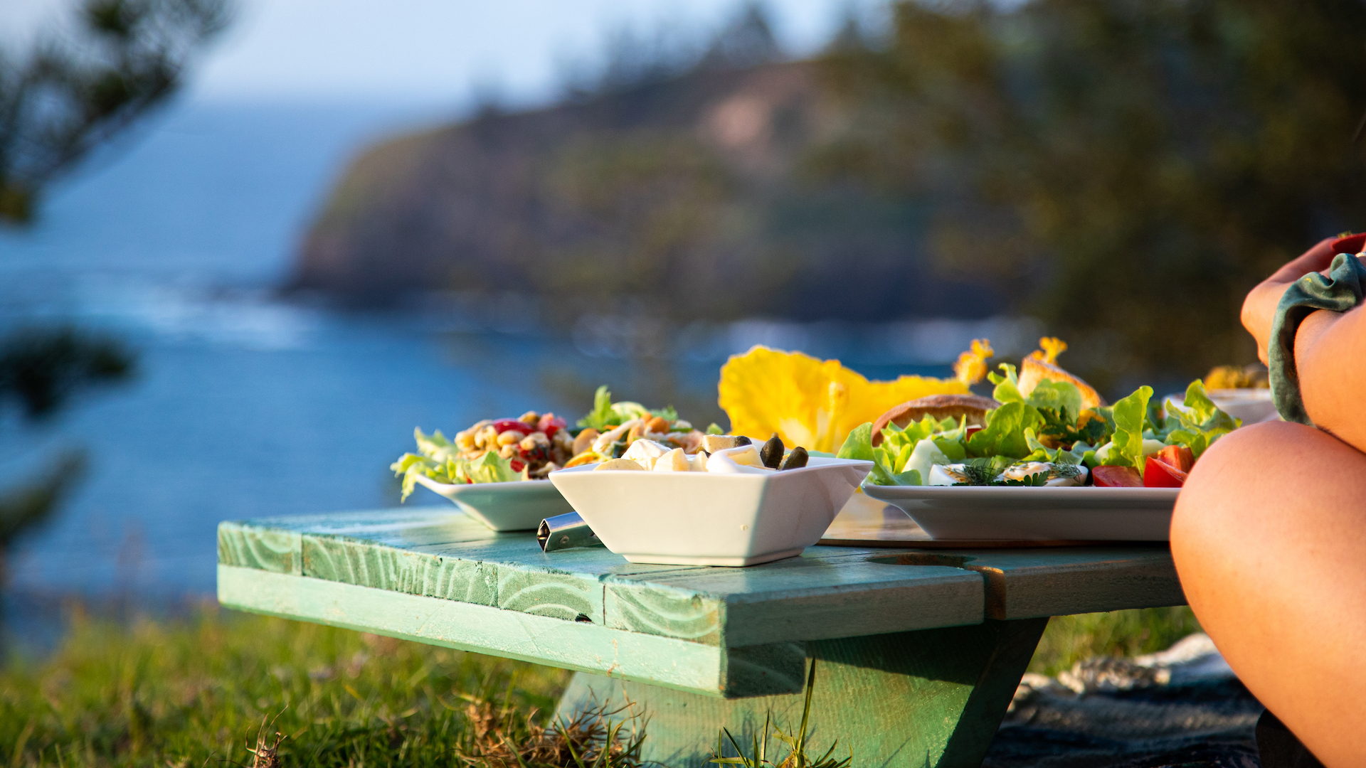 A detailed shot of fresh picnic food with ocean and cliffside in the background.