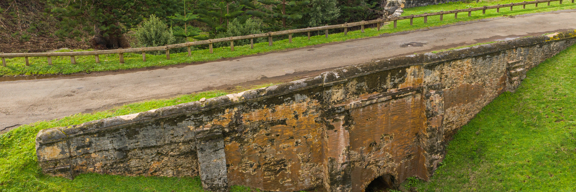 Side view of historic stone bridge, Bloody Bridge, fenced on one side and surrounded by sloping grass and pine trees.